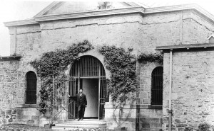An unidentified man poses at the entrance to the guardhouse, circa 1907 at the Bucks County Prison. Photo taken from James A. Michener Art Museum Archives.
