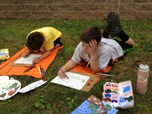 "Drawing and Painting students find inspiration for tree paintings in the shade near Steve Tobin's ""Romeo and Juliet."""